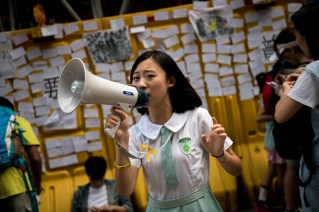 A girl in a school uniform urges people to write notes of support and their hopes for pro-democracy protests in Hong Kong on October 1, 2014. Hong Kong has been plunged into the worst political crisis since its 1997 handover as pro-democracy activists take over the streets following China's refusal to grant citizens full universal suffrage. AFP PHOTO / ALEX OGLE / AFP PHOTO / Alex Ogle